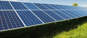Solar power panels on green field with blue sky and copy space and text area